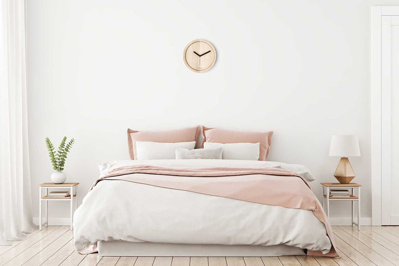 EORA design wall clock in a minimal white bedroom (pure ash wood)
