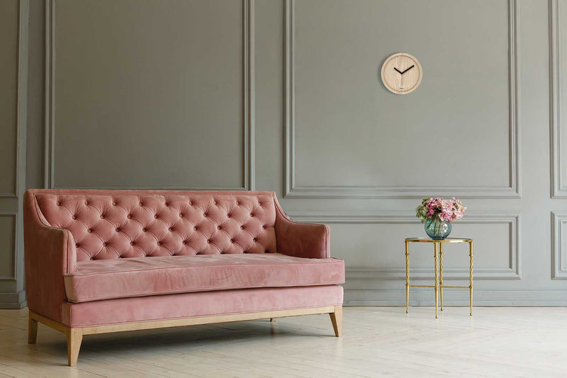 Eora design wall clock in a minimal room with a sofa (pure white ash wood)