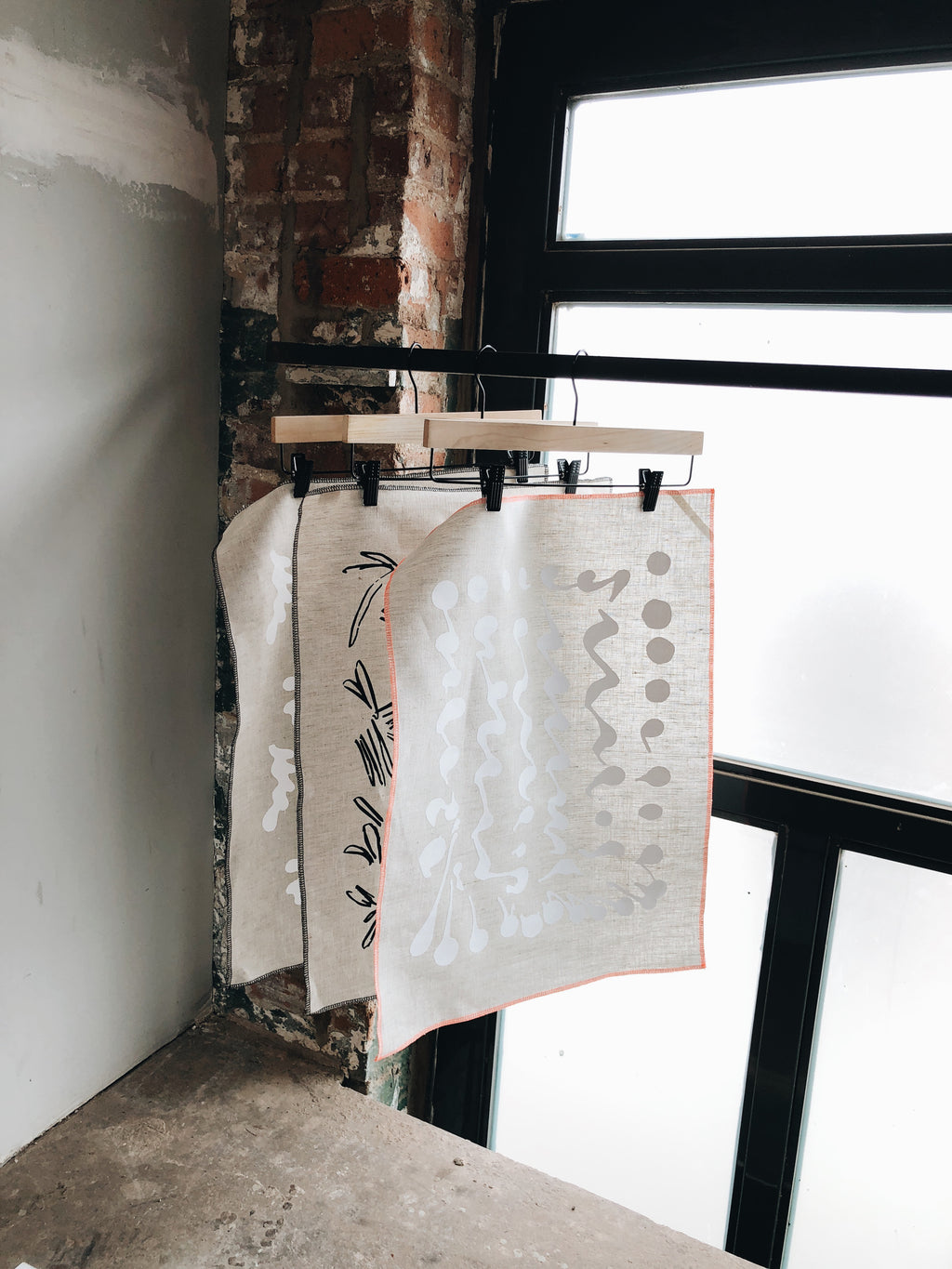 4: Three Patterned Tea Towels Hanging By A Window - LEIF