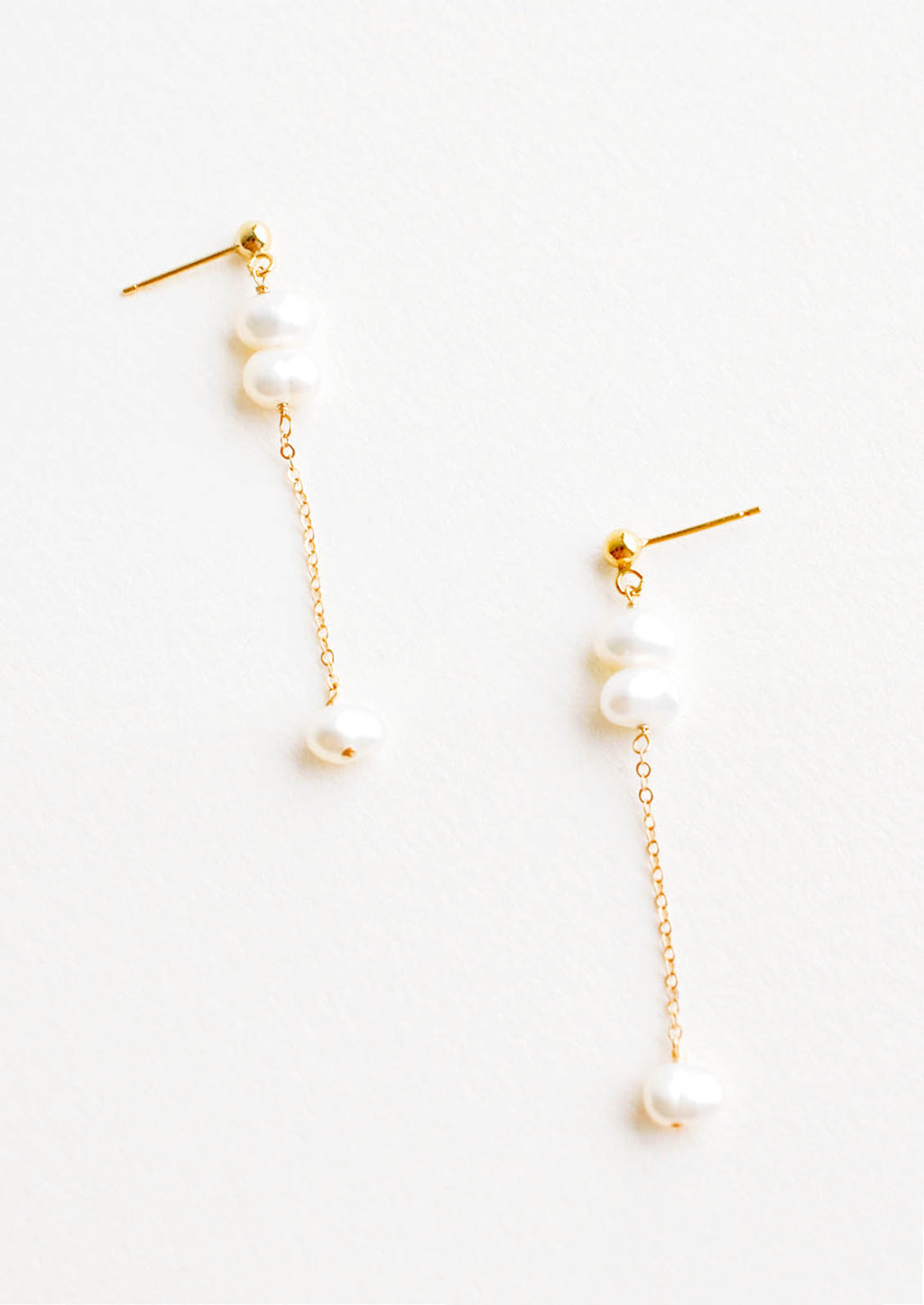 1: A pair of gold earrings with three pearls dangling from a post, and the third pearl is hanging from a fine gold chain.