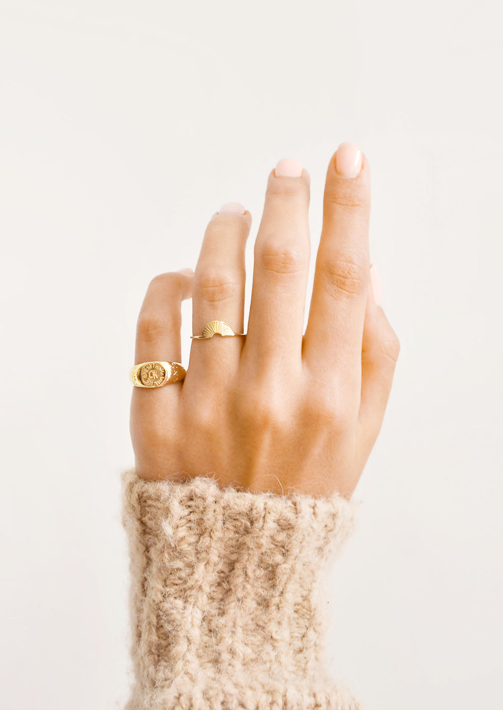 2: Model shot of hand wearing two gold rings.