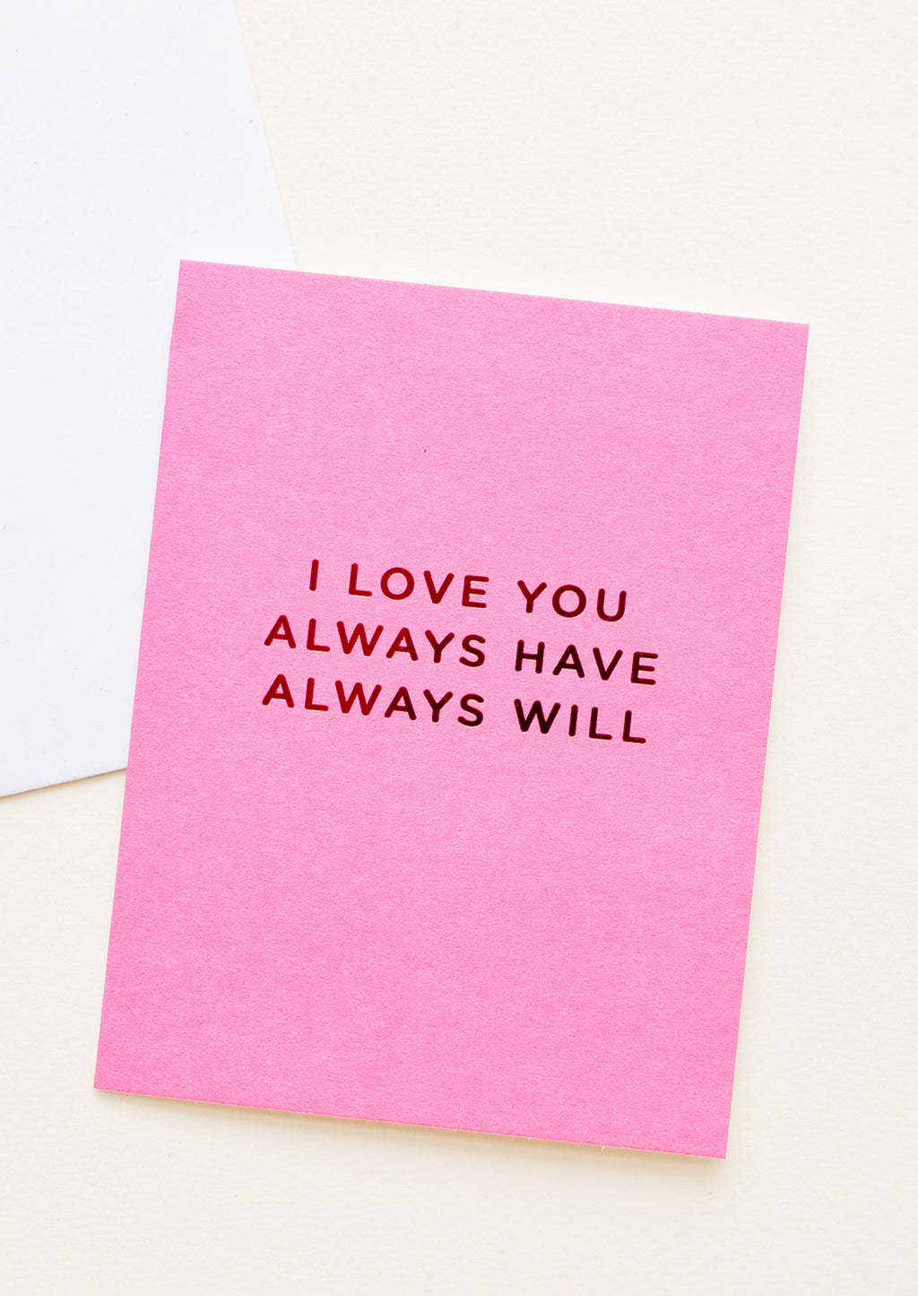 "1: A bright pink greeting card with ""I love you always have always will"" in red foil."