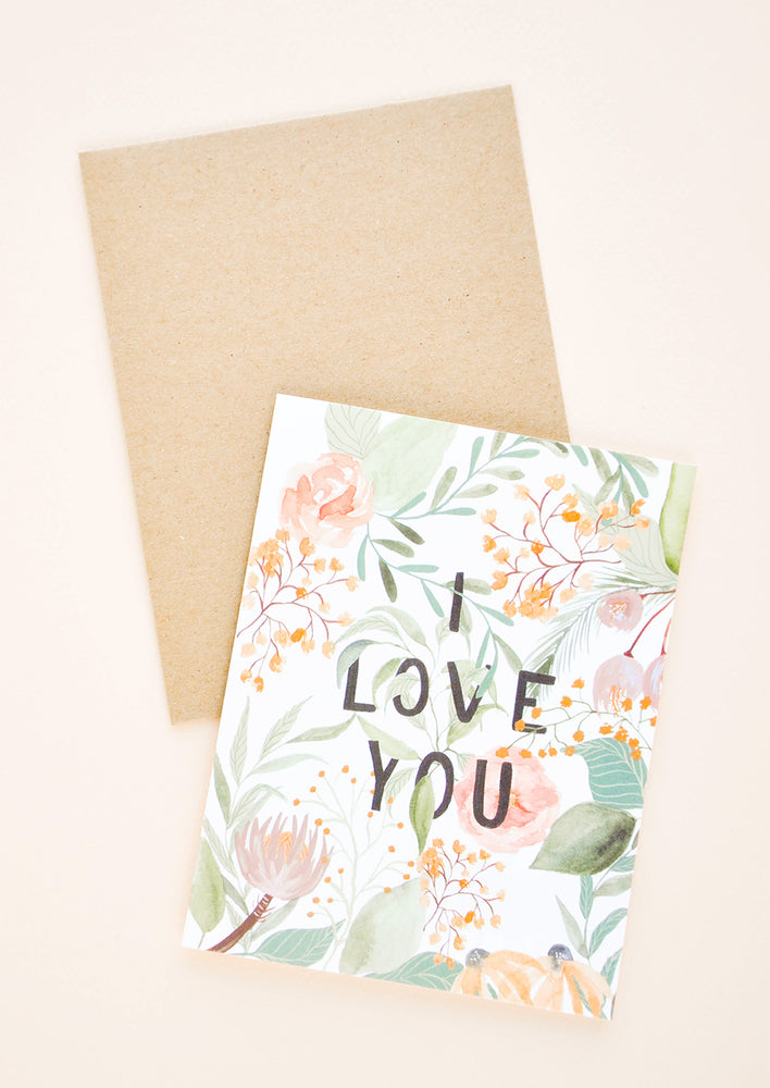 "1: A greeting card with watercolor floral motif and the words ""I love you"" in all caps peeking through the florals."