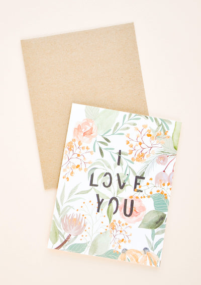 "A greeting card with watercolor floral motif and the words ""I love you"" in all caps peeking through the florals."