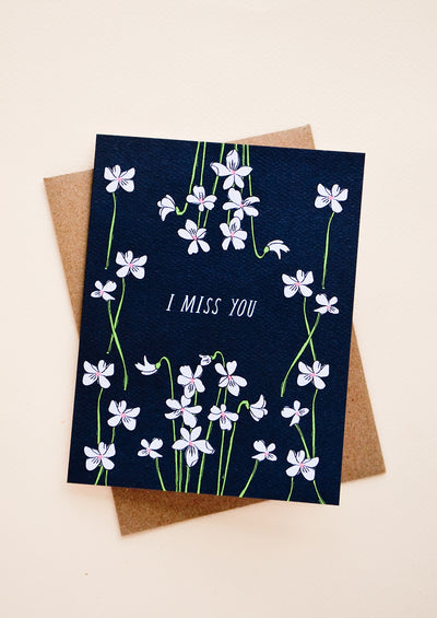 "Black greeting card with ""I Miss You"" written at center, surrounded by violet flowers"
