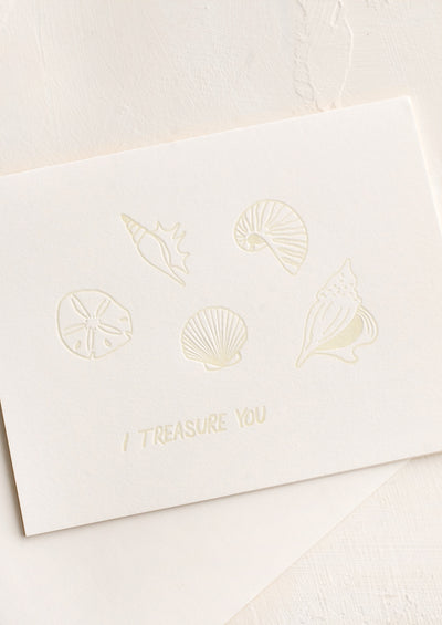 "A greeting card with seashells and text reading ""I treasure you""."