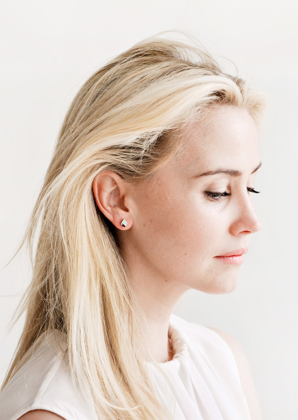 2: Blonde model wearing diamond shaped stud earrings.