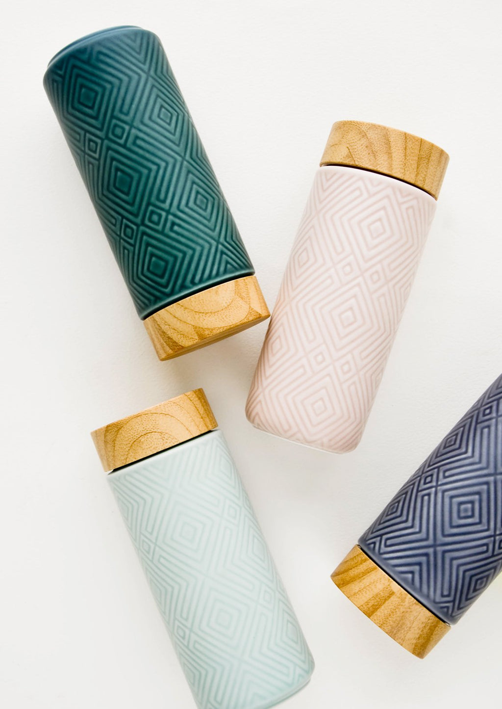 1: A scattered grouping of tall ceramic travel tumblers with tonal geometric patterns
