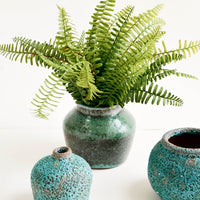 4: Group of heavily textured turquoise vases, pictured with a fern bouquet