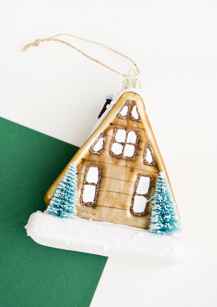 1: A glass ornament in the shape of an A frame house with two trees out front.