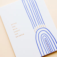 "2: White greeting card with cobalt blue rainbow and gold text reading ""After the rain comes the rainbow"""