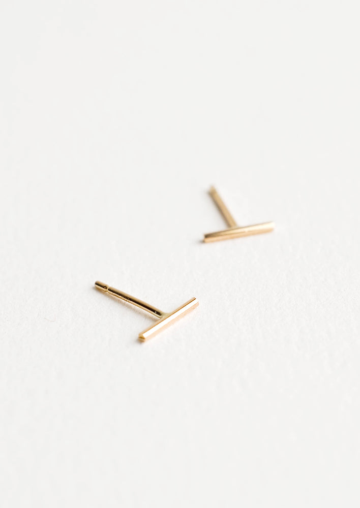 1: Close up of thin gold bar post back stud earrings.