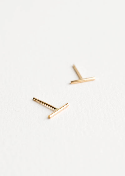 Close up of thin gold bar post back stud earrings.
