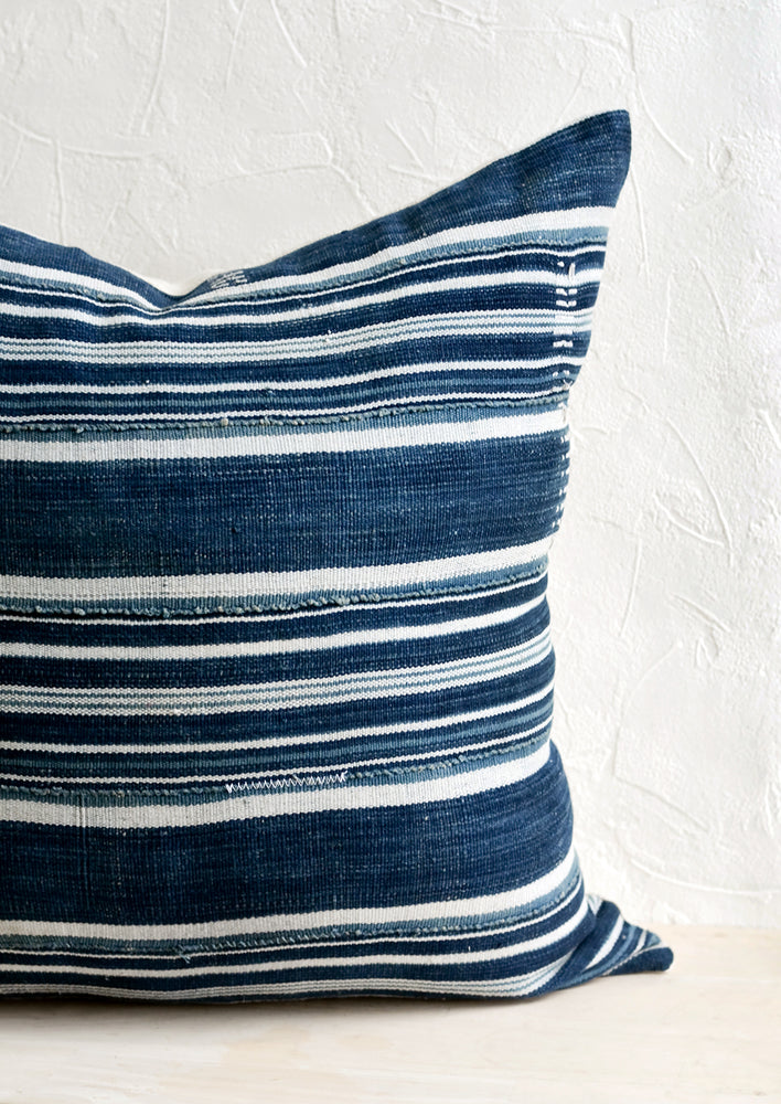 1: A throw pillow made from dark indigo fabric with white stripes and embroidery detailing.