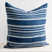 2: A throw pillow made from dark indigo fabric with white stripes and embroidery detailing, on a bench.