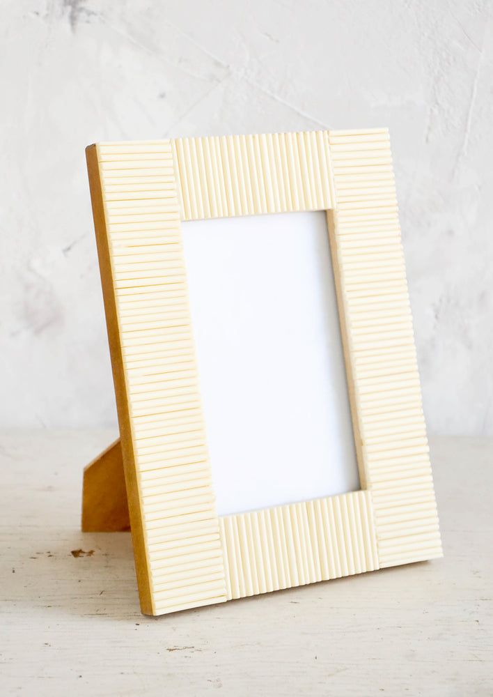 1: Empty picture frame on table. Frame is cream colored with ribbed texture made from bone.