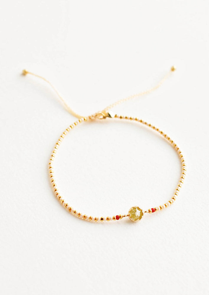 1: Delicate bracelet of white and gold beads and a yellow crystal charm flanked by two red beads.
