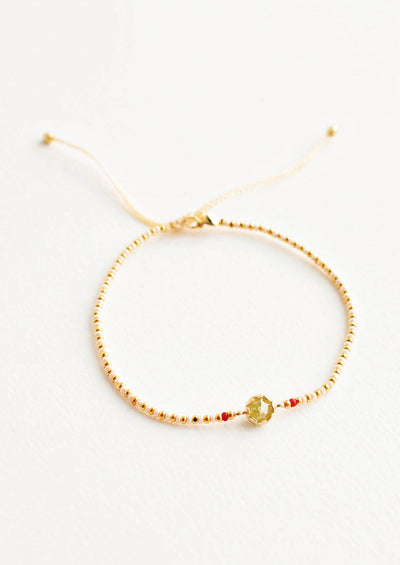 Delicate bracelet of white and gold beads and a yellow crystal charm flanked by two red beads.