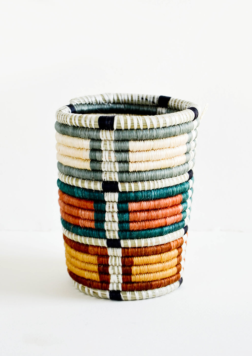 Grey Multi: Pencil cup shaped baskets woven from multicolor sweetgrass. Mix of muted colors in a square geometric pattern.