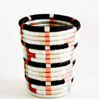 Peach Multi: Pencil cup shaped baskets woven from multicolor sweetgrass. Mix of pastel colors in a geometric pattern.