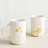 2: Two white ceramic mugs with hand painted peach and mustard glaze drips.
