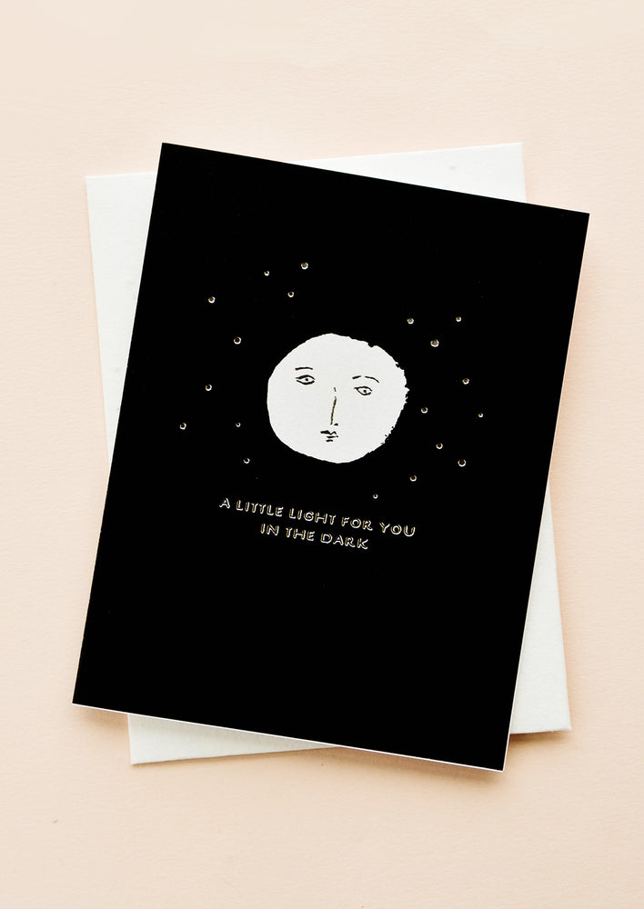 "1: Black greeting card with white moon and silver text ""A little light for you in the dark"""