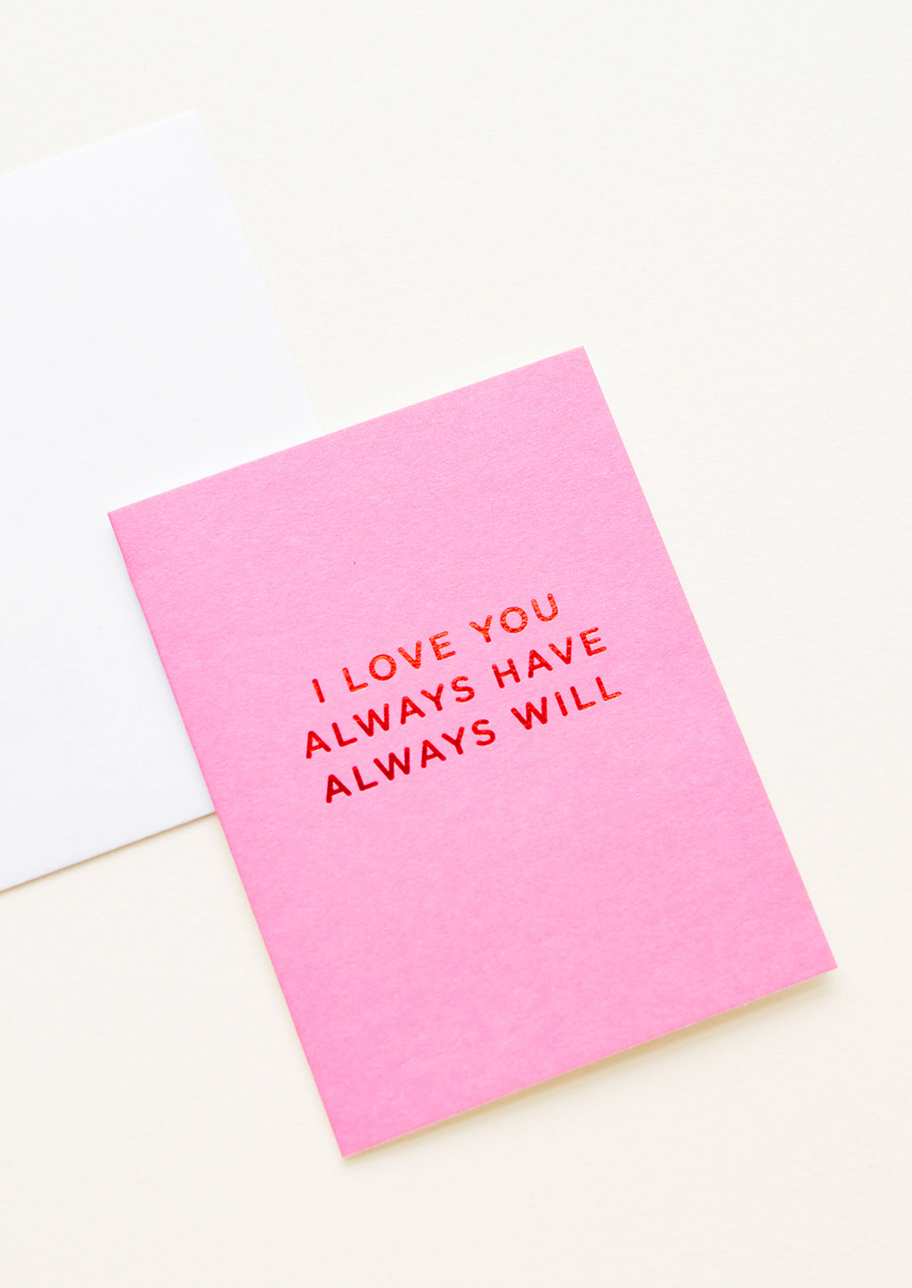 "2: A white envelope and bright pink greeting card with the words ""I love you always have always will"" in red foil."