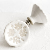 Floral: White ceramic cabinet knobs with floral relief pattern.