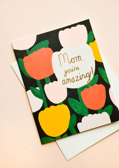 "Greeting card with tulips printed on black background, text reads ""Mom, you're amazing!"""