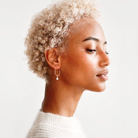 2: Model wears delicate gold and opal drop earrings and white sweater.