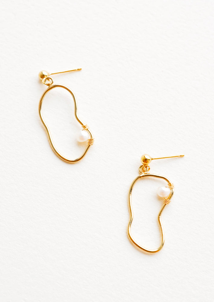 1: Dangling earrings featuring asymmetric round gold charm made from a slim gold hoop, with one pearl attached with wrapped wire.