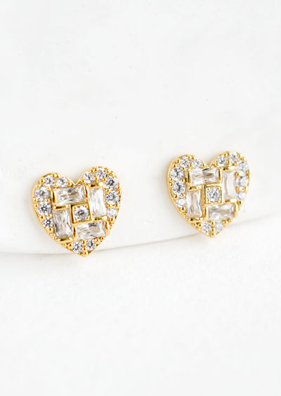 A pair of gold heart shaped stud earrings with a mix of rectangular and round crystal pave detailing.
