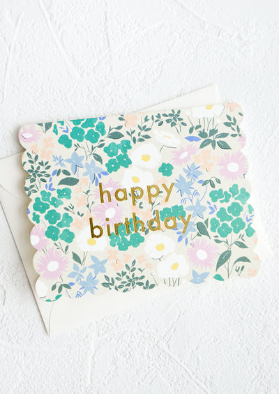 "Greeting card with die cut scalloped edges, allover floral print and ""Happy birthday"" printed in gold"