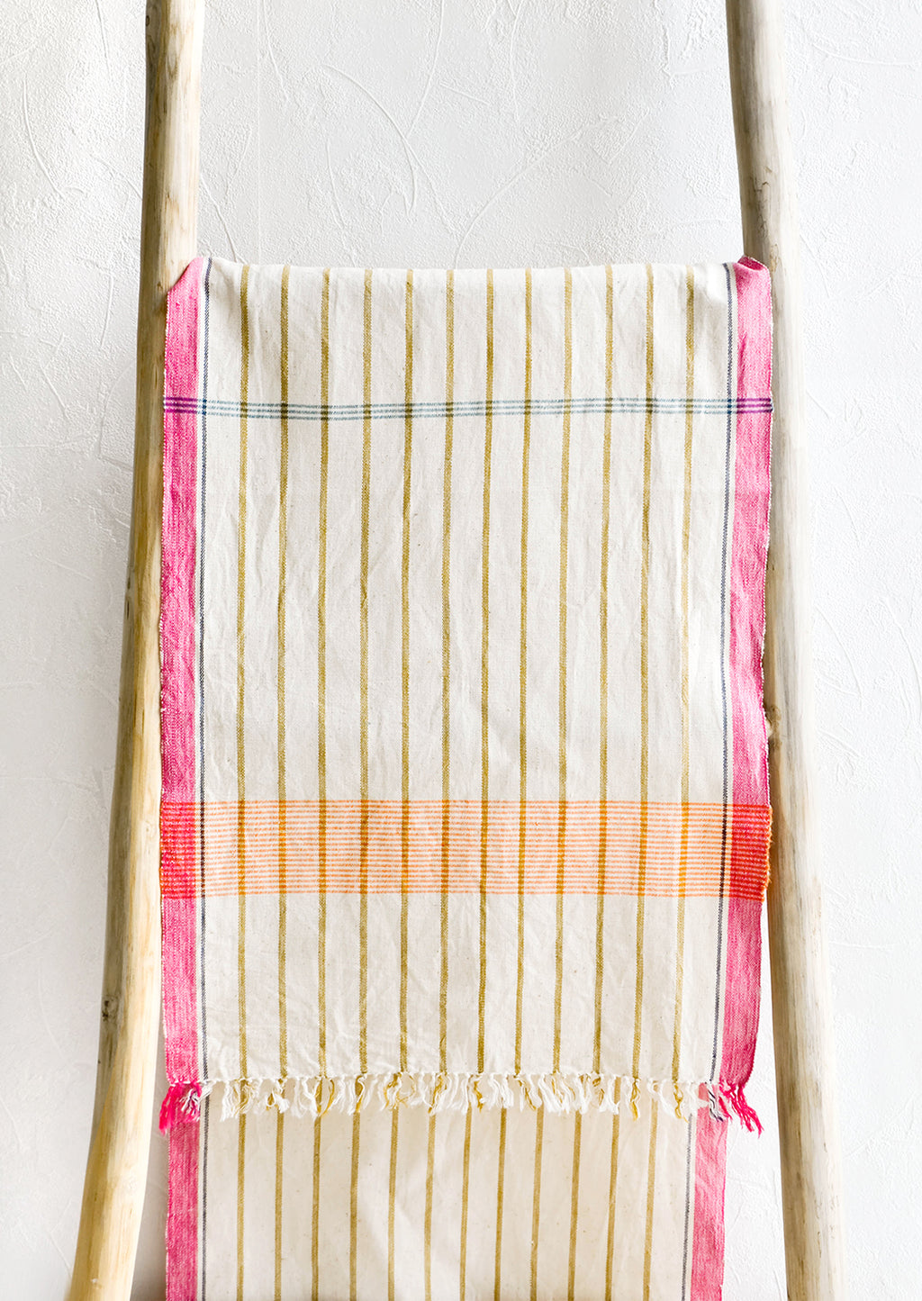 2: Brightly colored cotton table runner displayed on wooden ladder