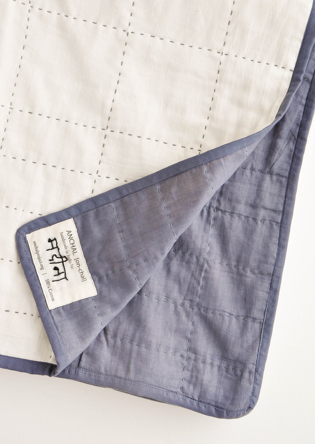3: Maker tag detail on slate blue colored side of reversible organic cotton quilt, featuring grid pattern stitching