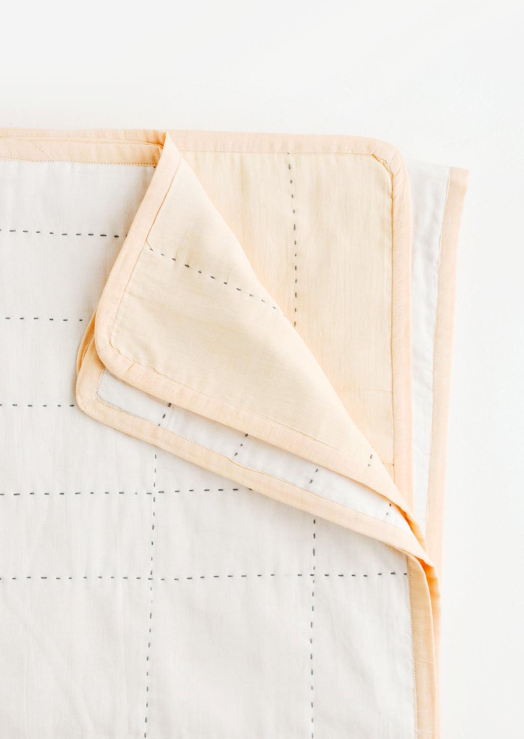 Peach: Reversible organic cotton quilt with embroidered grid pattern in peach and ivory with black stitching