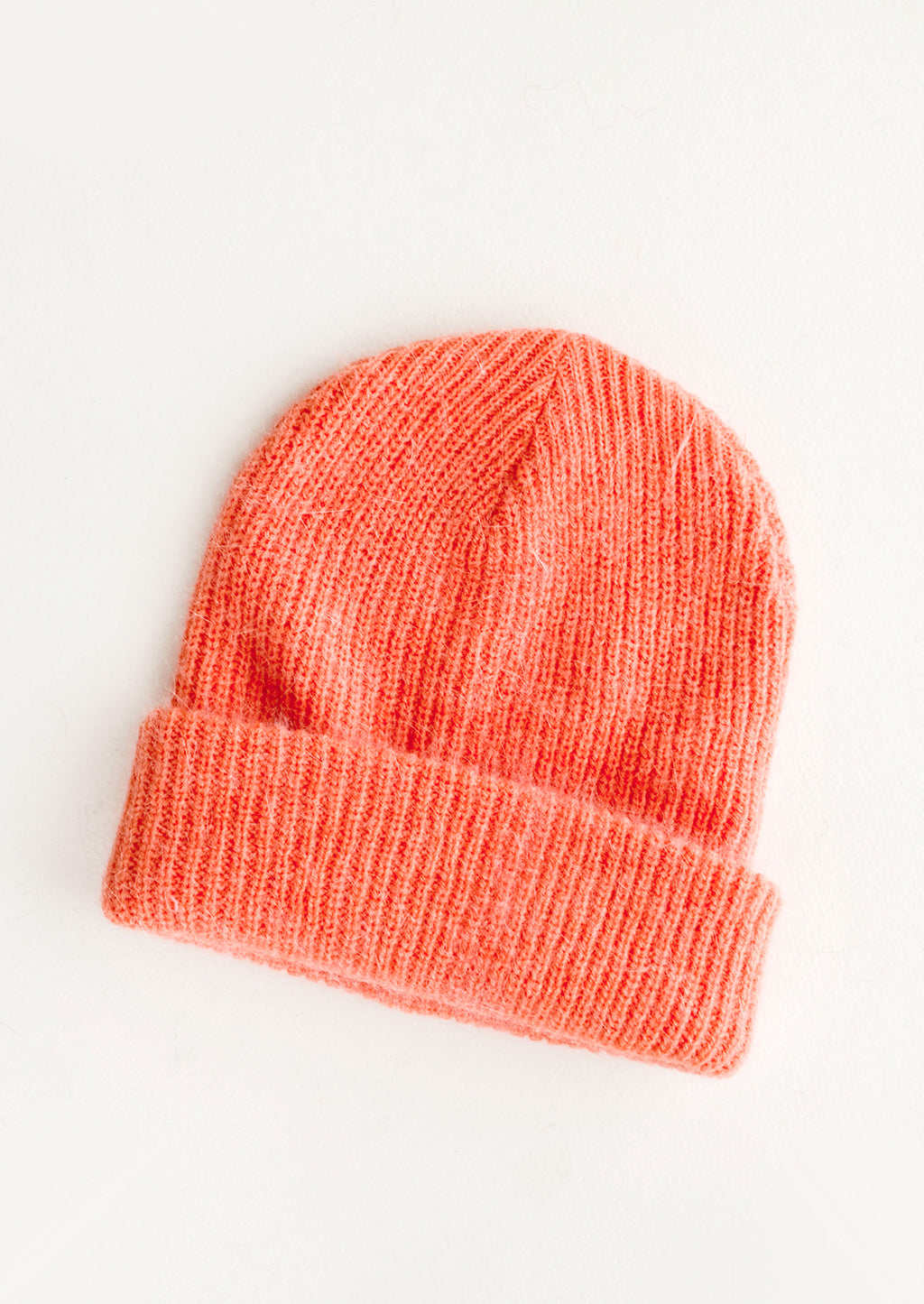Coral: Coral knit beanie with fold.
