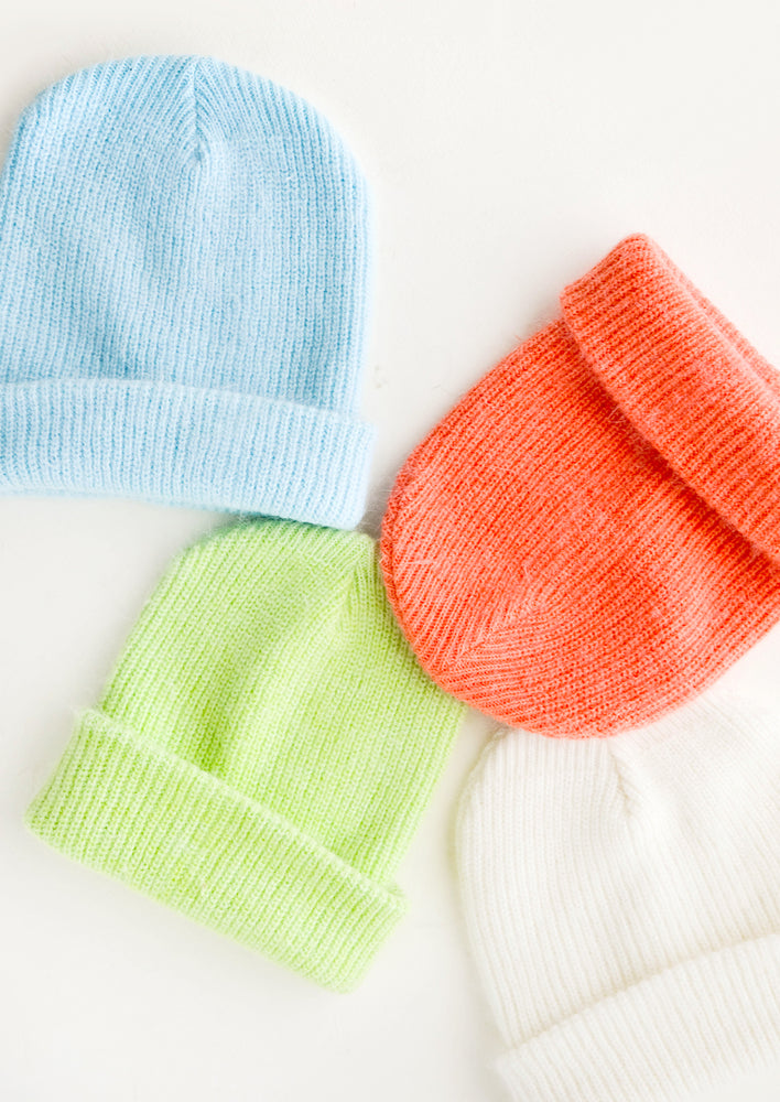 1: Four knit beanies in blue, lime green, coral, and ivory.