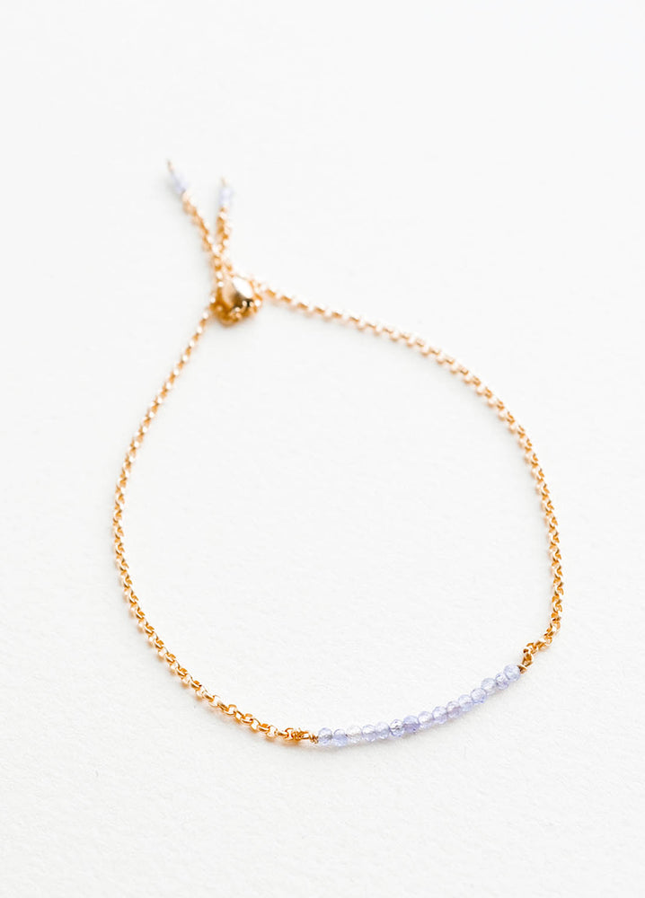 Tanzanite: A delicate gold chain bracelet featuring a row of miniature light blue gemstones.
