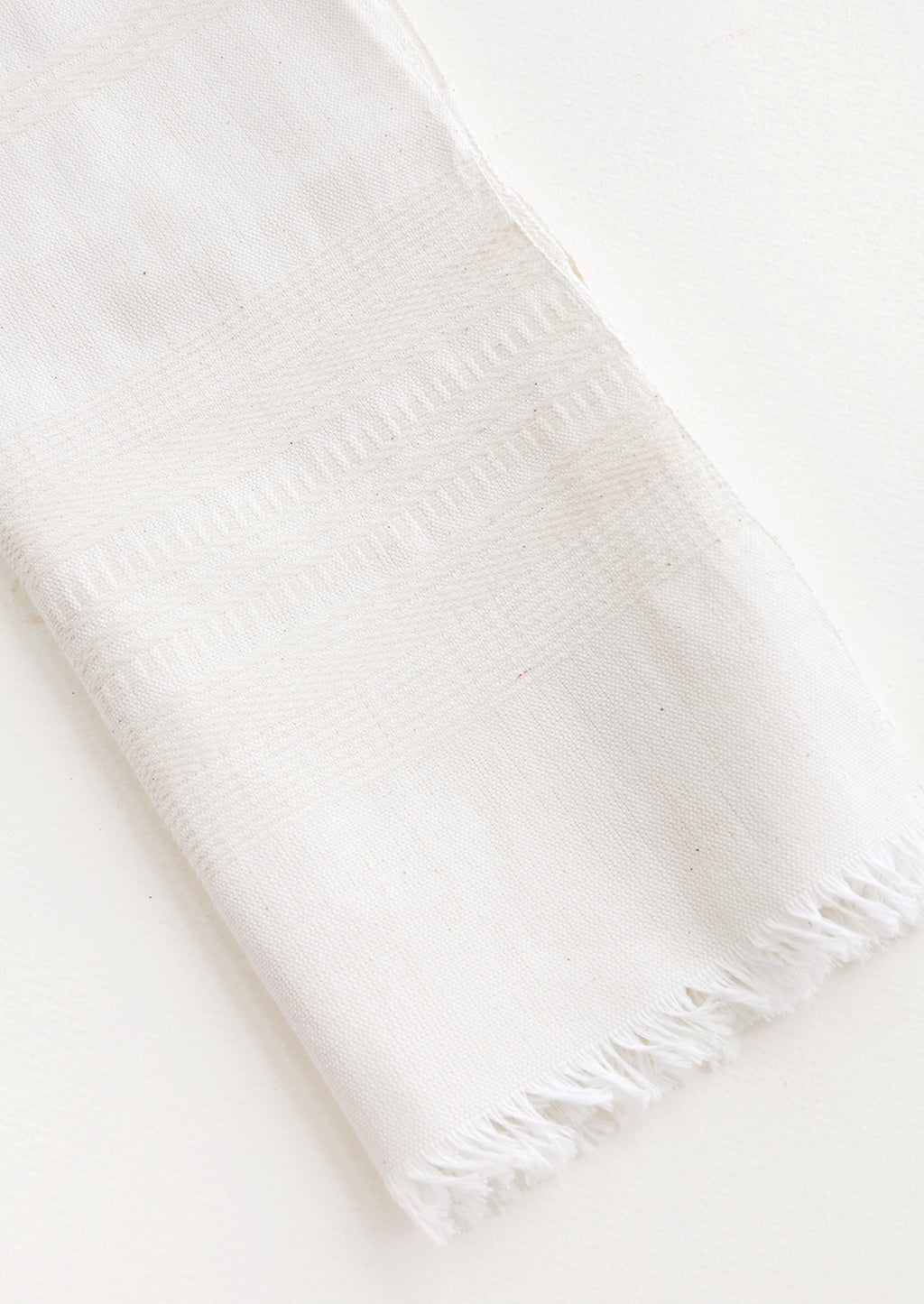 Unbleached: A white cotton towel with fringed edge.