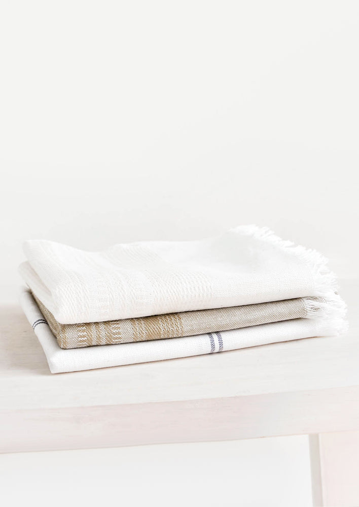 1: Three folded cotton towels stacked neatly in a pile.