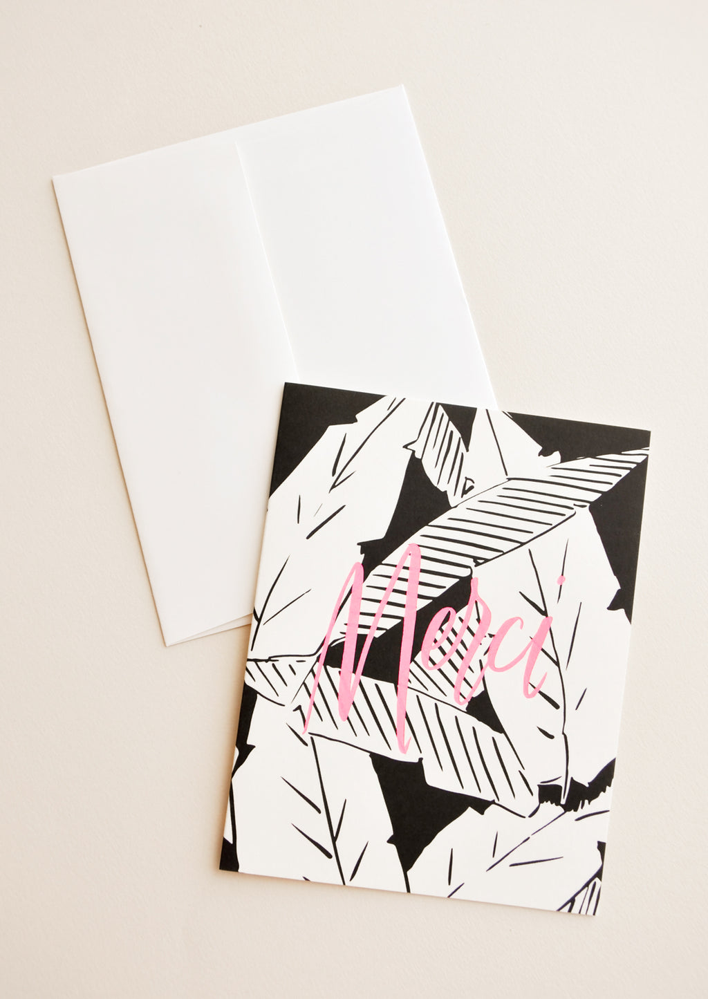 "1: Notecard with black and white palm leaves decoration and the word ""Merci"" in pink, and white envelope."