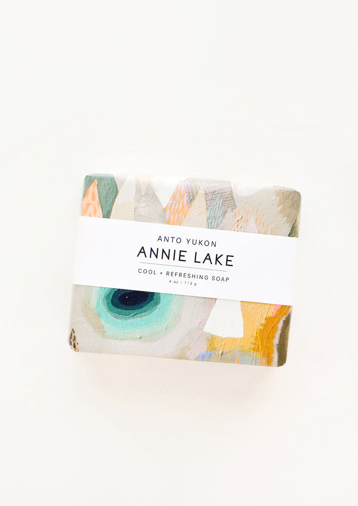 Annie Lake: A bar of soap in multicolored packaging with a white horizontal label.
