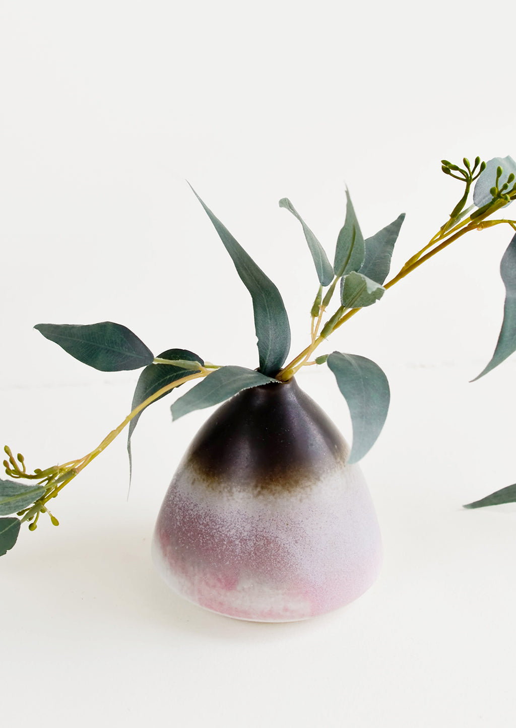1: Round tapered bud vase with narrow top and wide bottom, brown at top transitions to purple at bottom. Shown displaying single eucalyptus branch.