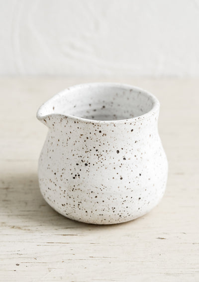 A small white pitcher in speckled ceramic.