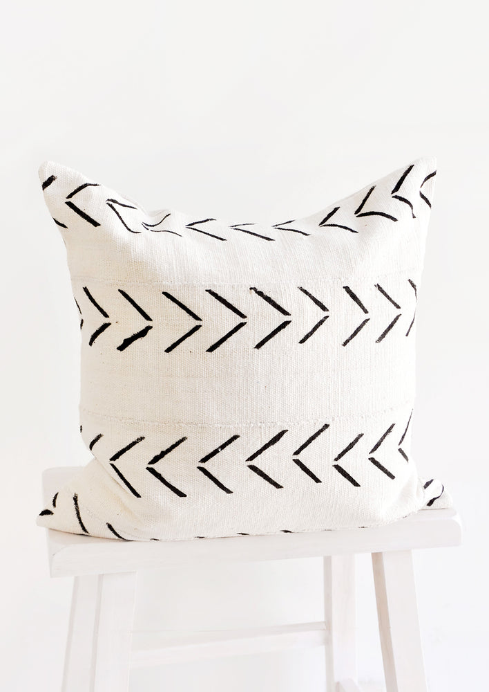 Square throw pillow in natural ivory mudcloth with horizontal printed rows of black arrows