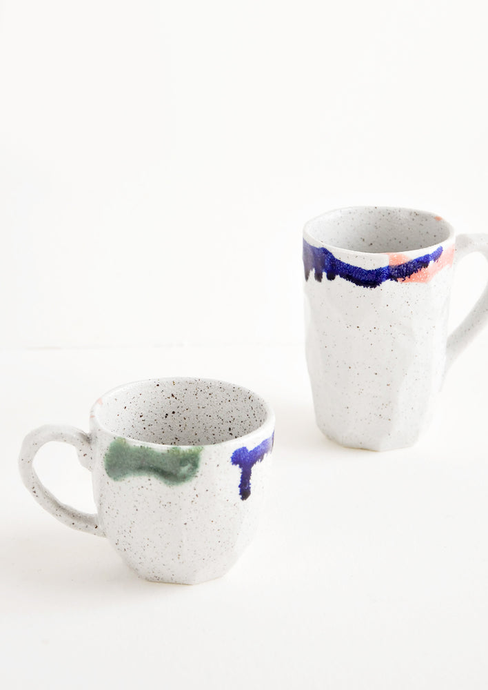 1: Two differently sized gray ceramic mugs with blue, green, and pink painted rims.