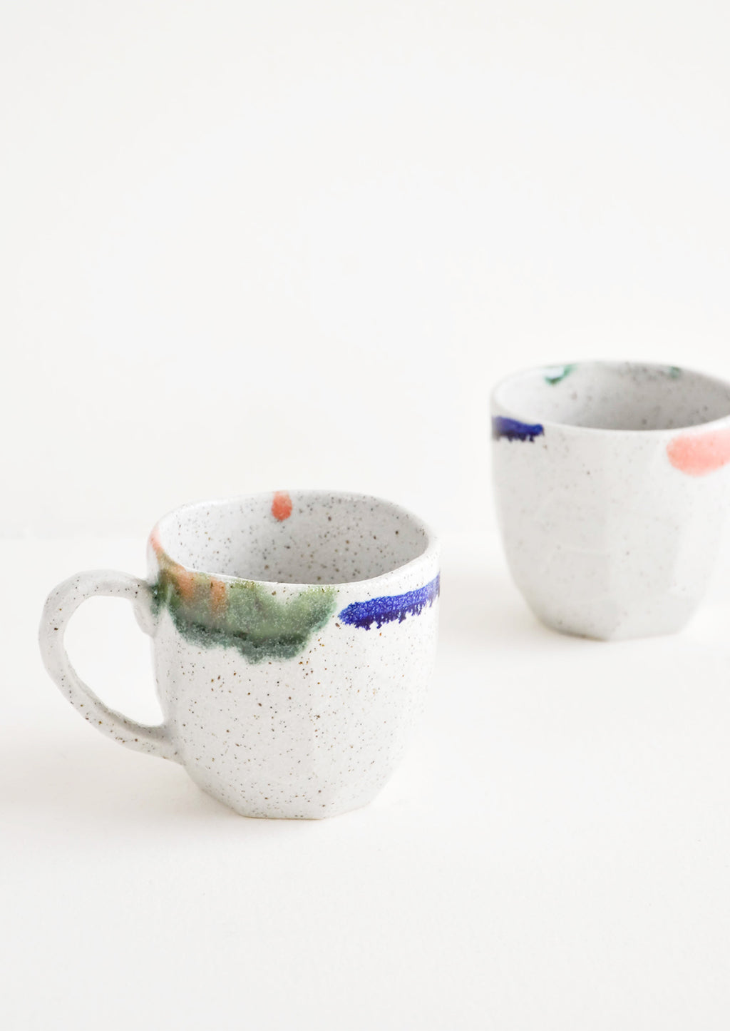 3: Two short gray ceramic mugs with blue, green, and pink painted rims.