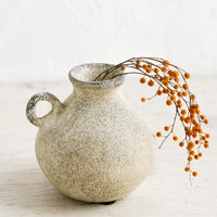 2: A petite ceramic bud vase in tan patina finish, holding dried mimosa sprig.