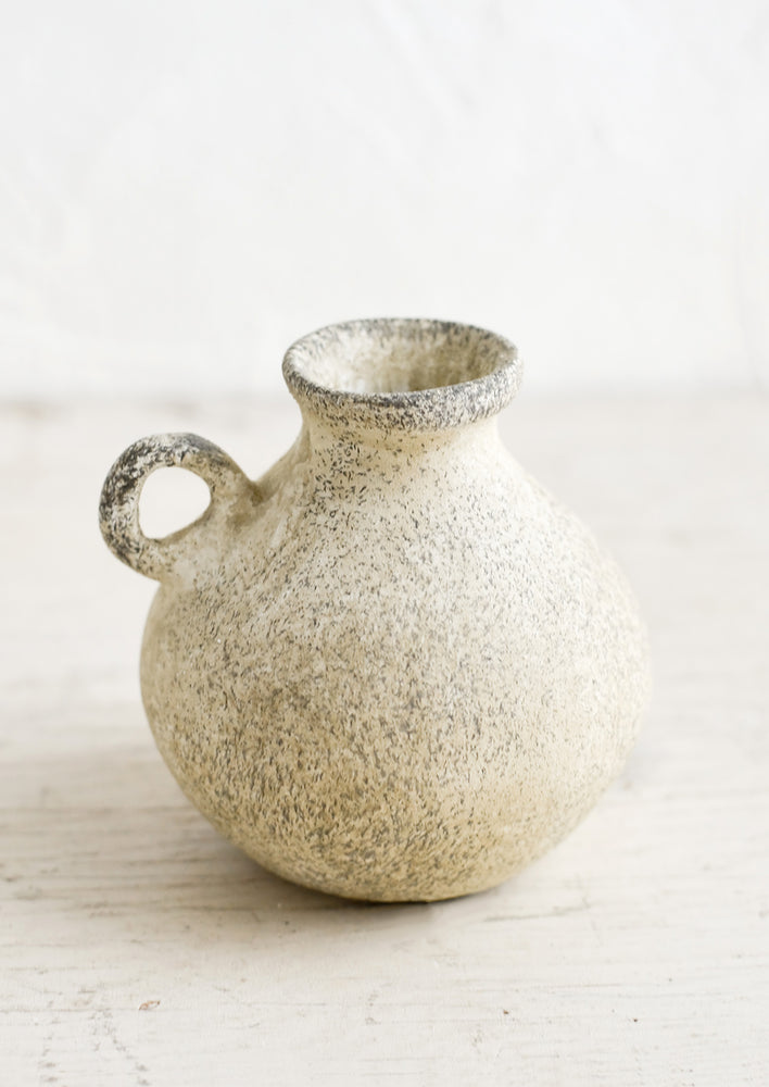A petite ceramic bud vase in tan patina finish.